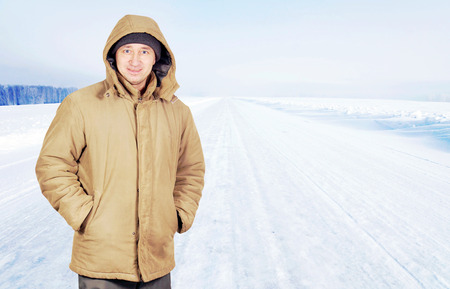 Happy man outdoor on an empty road in cold winter day Stock Photo