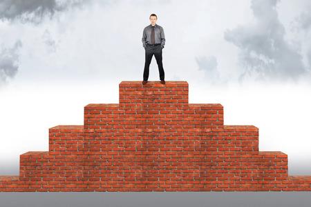Assertief man staat op de top van een bakstenen piramide. Concept van succes