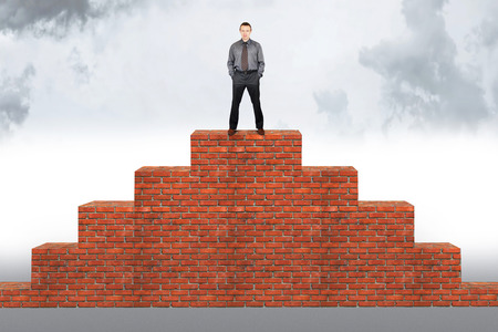 Assertive man stands on the top of a brick pyramid. Concept of success