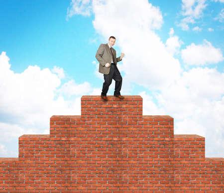 climbed: Joyful man climbed on the brick pyramid. Concept of success