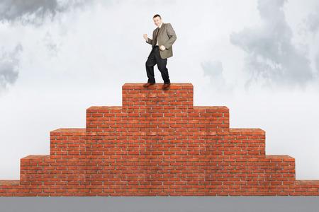Happy man climbed on the brick pyramid. Concept of success photo