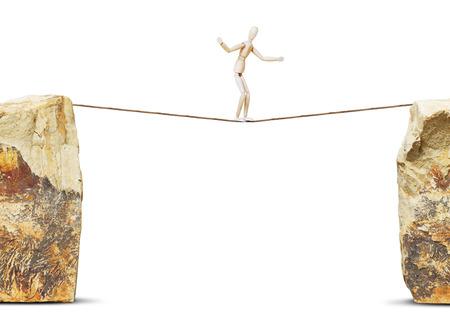 marioneta de madera: El hombre pasa a lo largo de una cuerda entre altas rocas. Concepto de peligro con un muñeco de madera Foto de archivo