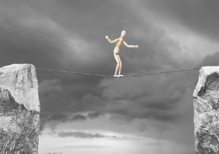 marioneta de madera: El hombre pasa a lo largo de una cuerda sobre el precipicio. Concepto de peligro con un muñeco de madera