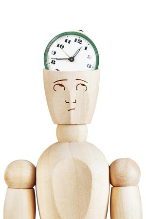 llegar tarde: despertador en la cabeza humana. apuros de tiempo. Imagen abstracta con una marioneta de madera