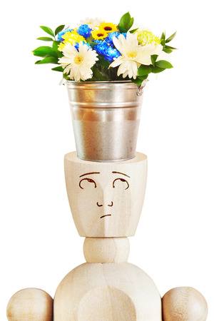 Bouquet of beautiful flowers in the bucket stands on a human head. Abstract image with a wooden puppet