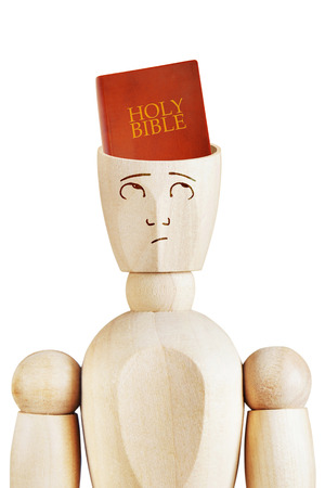 marioneta de madera: Holy Bible in the human head. Religious mind. Abstract image with a wooden puppet