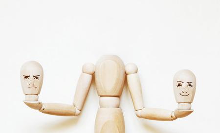 marioneta de madera: Hombre sin cabeza tiene dos cabezas con diferentes emociones. Imagen abstracta con una marioneta de madera Foto de archivo