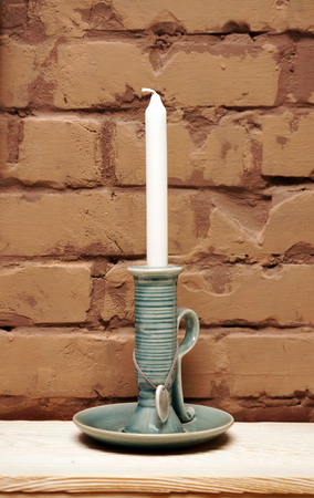 Candlestick with a candle by the brick wall
