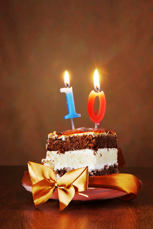 number ten: Piece of Birthday Chocolate Cake with Burning Candle as a Number Ten on Brown Background