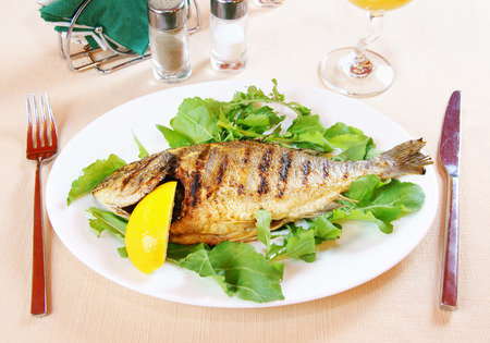 Fried fish Dorada with lemon and greenery