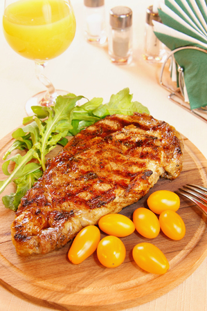 Ribeye steak with fresh greenery and tomatoes