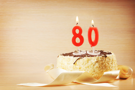 Birthday cake with burning candle as a number eighty. Focus on the candle