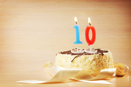 numero diez: Birthday cake with burning candle as a number ten. Focus on the candle