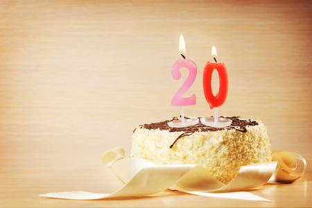 Birthday cake with burning candle as a number twenty. Focus on the candle Stock Photo