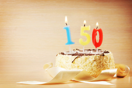 Birthday cake with burning candle as a number one hundred and fifty. Focus on the candle