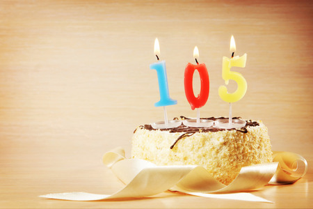 Birthday cake with burning candle as a number one hundred and five. Focus on the candle