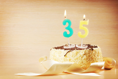 Birthday cake with burning candle as a number thirty five. Focus on the candle Stock Photo