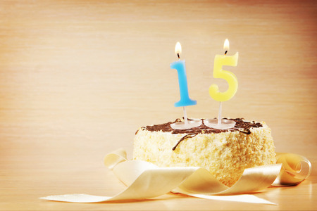 Birthday cake with burning candle as a number fifteen. Focus on the candle
