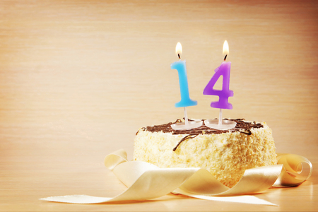 fourteen: Birthday cake with burning candle as a number fourteen. Focus on the candle