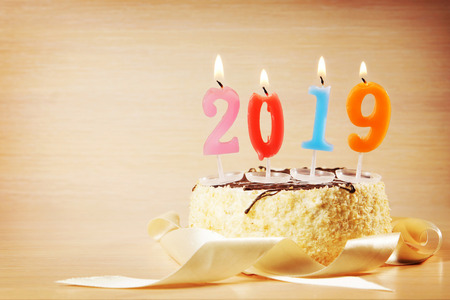 New Year 2019 composition. Cake and burning candles against brown background