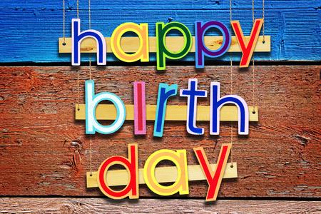 clavados: Feliz cumpleaños. Luz brillante, letras pintadas de colores sobre fondo de madera grunge Foto de archivo