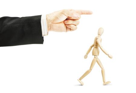 obediencia: Hombre que va en la dirección que se muestra. Concepto de obediencia completa. Imagen abstracta con una marioneta de madera Foto de archivo