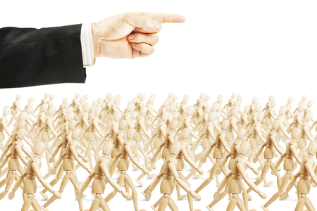 subjugation: Many people going in shown direction. Concept of full obedience. Abstract image with a wooden puppet Stock Photo
