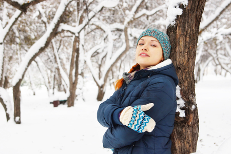 leaned: Portrait of happy beautiful girl leaned to the tree in winter park Stock Photo
