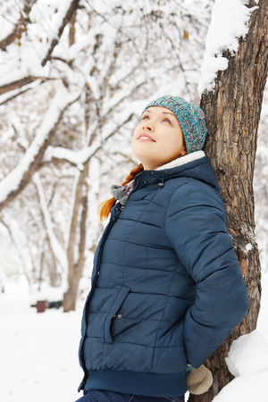 leaned: Happy beautiful girl leaned to the tree in winter park and relaxes