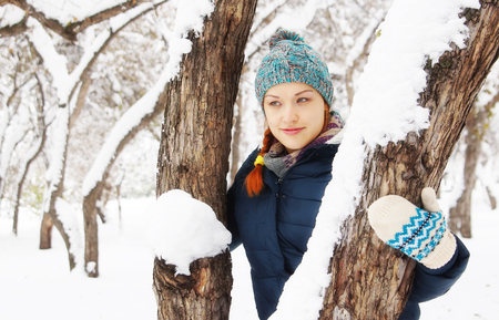 Happy beautiful young woman has a rest in winter park