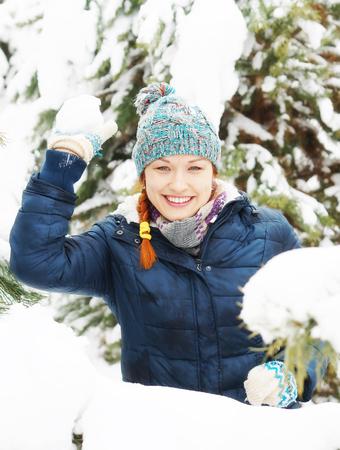 palle di neve: Joyful happy pretty girl plays snowballs in winter pine forest