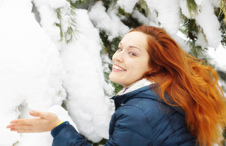 rejoices: Beautiful long-haired redhead girl rejoices of fresh air in snowy winter forest