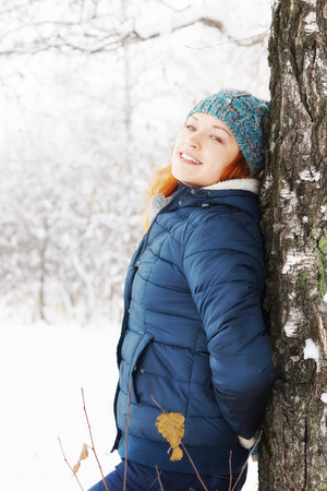 leaned: Beautiful young woman leaned to the birch in winter forest and has a rest