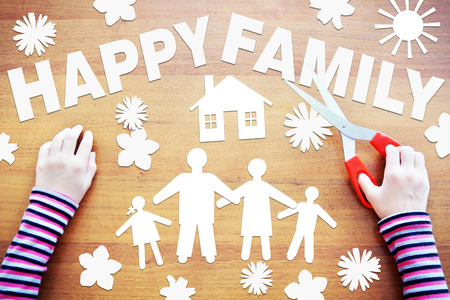 fantasize: Little girl makes composition about happy family. Abstract image with paper scrapbooking Stock Photo