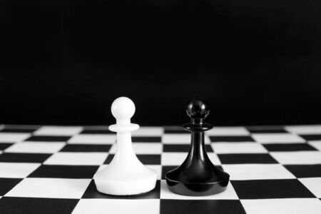 contender: Black and white chess pawns. Battle of equal rivals. Concept with chess pieces against black background Stock Photo