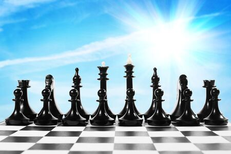 chessman: Set of black chess pieces on the chessboard against bright blue sky