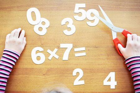 multiplicar: La niña está aprendiendo a multiplicar. Concepto con el álbum de recortes de papel