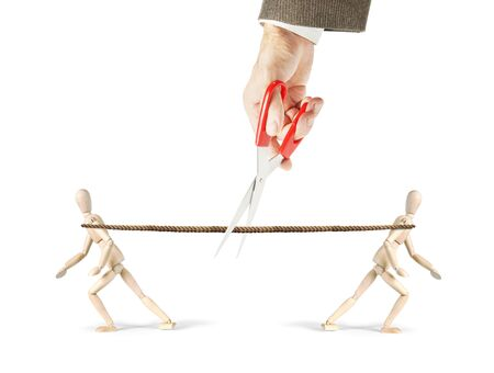 Man cuts a rope which two men pull in different directions. Get rid from competition. Abstract image with wooden puppets Stock Photo