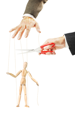Man cuts threads of a wooden puppet. Concept of release and stopping manipulation Stock Photo
