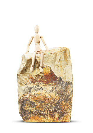 marioneta de madera: Man sitting on a high rock. Abstract image with a wooden puppet