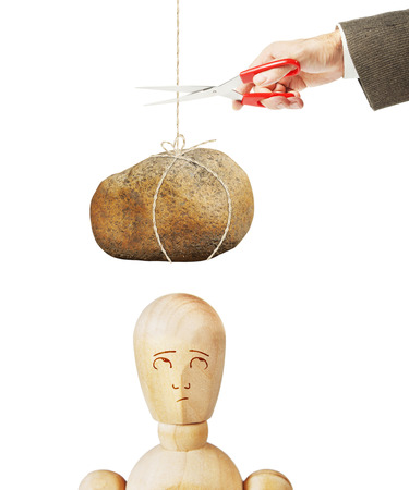 heavy risk: Man cuts the thread with large stone to fall it on another person. Abstract image with a wooden puppet Stock Photo