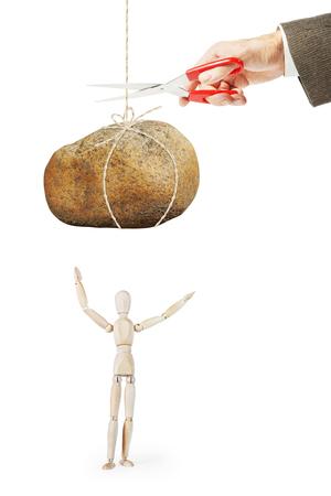 marioneta de madera: El hombre corta el hilo con gran piedra para dejarla caer sobre otra persona. Imagen abstracta con una marioneta de madera