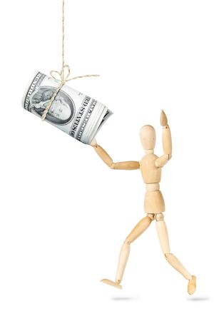 Man wants to catch a roll of dollars banknotes hanging above. Abstract image with a wooden puppet