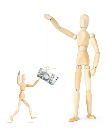 Man teases another person with a bundle of dollars which hanging on a thread. Abstract image with wooden puppets Stock Photo