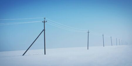 snowy field: Winter landscape with power pillars at the deserted snowy field Stock Photo