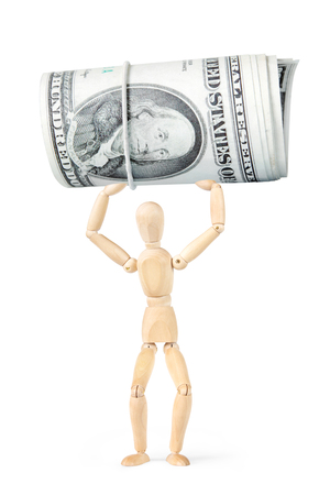 Man picks up a huge roll of dollar banknotes. Abstract image with a wooden puppet Stock Photo
