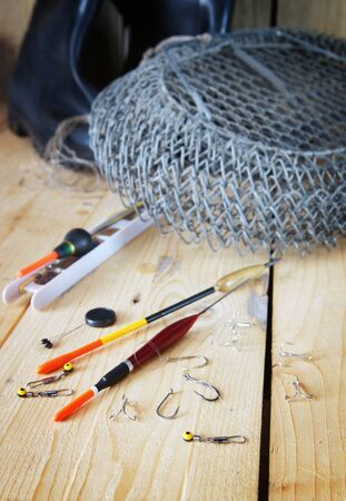 fishing floats: Vertical composition with various fishing floats and angling cage on wooden background Stock Photo