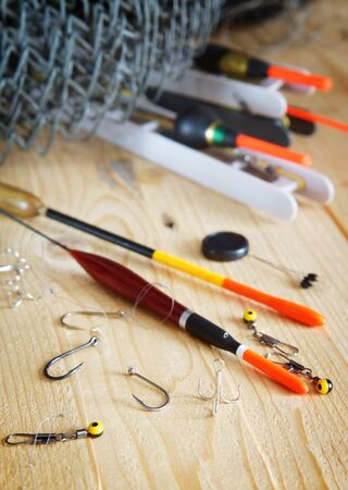 fishing floats: Vertical composition with various fishing floats and other tackles on wooden background Stock Photo