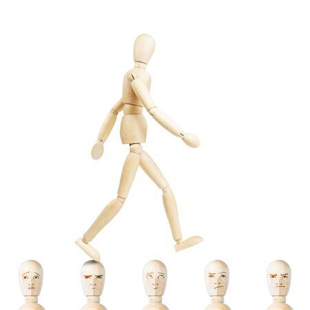 marioneta de madera: El hombre va por delante en las cabezas de otras personas. Concepto de la arrogancia y la soberbia. Imagen abstracta con una marioneta de madera