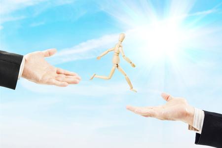 marioneta de madera: El hombre salta de una palma de la mano masculina a otro. Imagen abstracta con una marioneta de madera